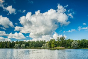 Beautiful russian landscape with trees near water of a lake and clouds in blue sky. Catherine park in Pushkin - Tsarskoe Selo, St.Petersburg, Russia. © Romas
